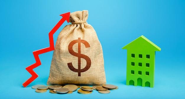 Sacchetto dei soldi del dollaro con la freccia rossa verso l'alto e l'edificio residenziale