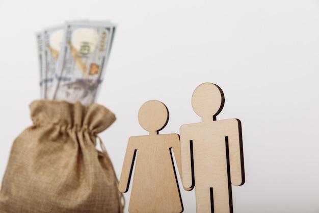 Borsa di denaro dollaro con figure in legno di persone su sfondo bianco. primo piano del concetto di risparmio familiare