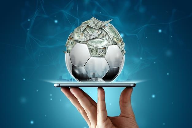 I dollari sono dentro il pallone da calcio, la palla è piena di soldi in uno smartphone. scommesse sportive, scommesse sul calcio, gioco d'azzardo, bookmaker, grande vittoria.