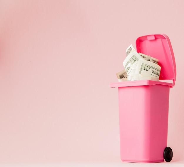 Banconote in dollari nel bidone della spazzatura rosa su