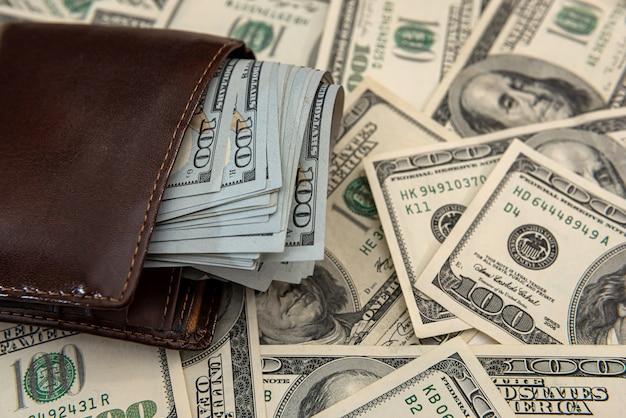 Banconote in dollari in un portafoglio in pelle scura, sfondo finanziario