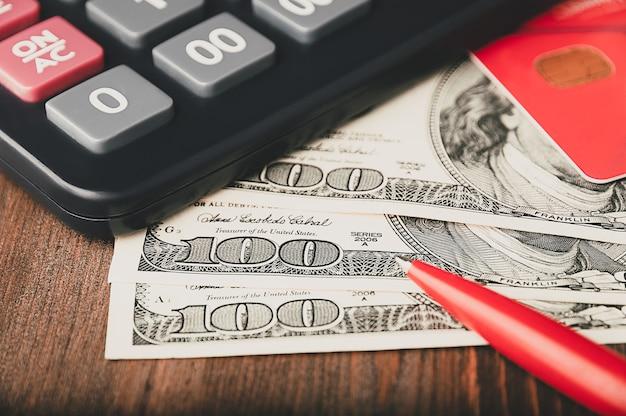 Dollari in banconote sono sparsi sul tavolo accanto a una calcolatrice