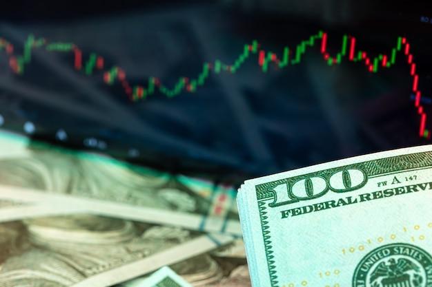 Dollari davanti a un monitor con un grafico dei prezzi. forex e trading. avvicinamento.