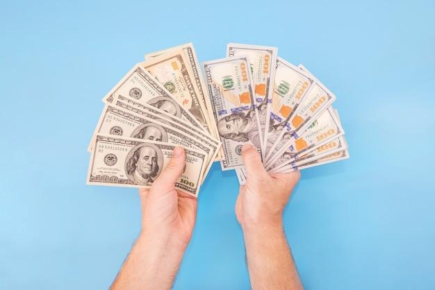 Dollari in mani maschili su sfondo blu.