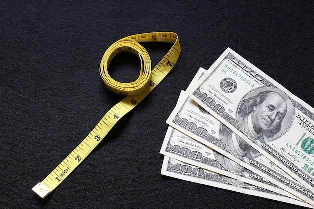 Dollari e un metro a nastro come simbolo del costo della perdita di peso