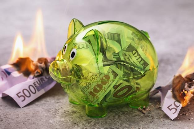 Dollari in un salvadanaio trasparente circondato da banconote in euro in fiamme il concetto di una forte valuta mondiale