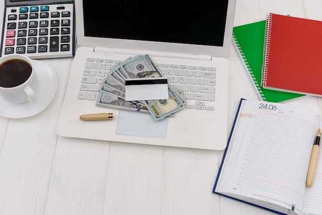 Dollari con vista dall'alto di laptop e diario