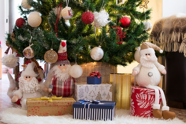 Bambole, regali e sorprese su un tappeto bianco, sotto l'albero di natale.