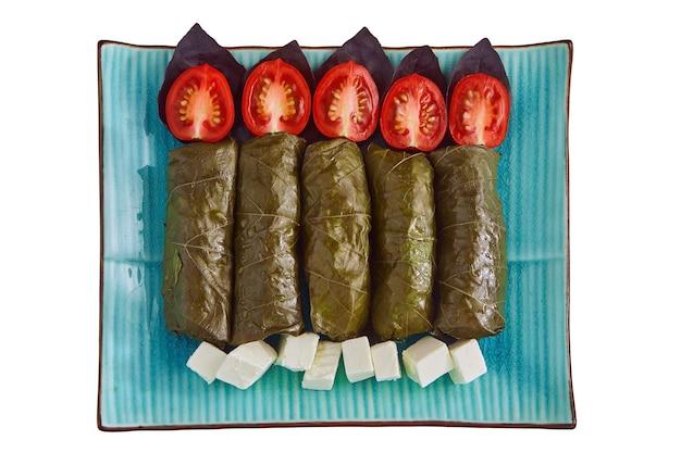 Dolma di foglie di vite con basilico, pomodori e feta su un piatto blu