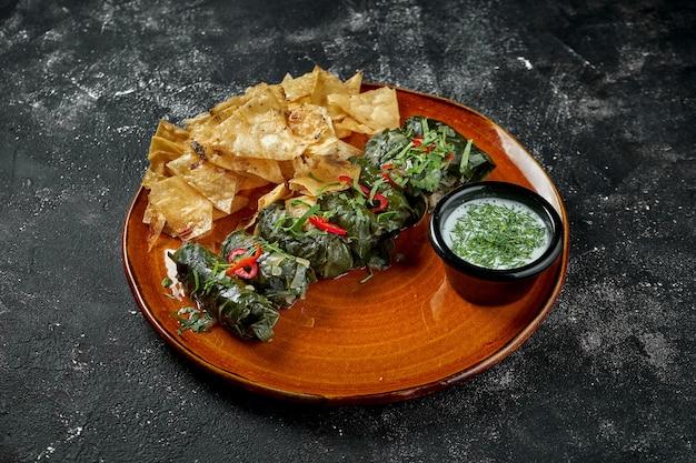 Dolma è un piatto caucasico nazionale. carne macinata avvolta in foglie di vite stufata in salsa con formaggio. foglie di vite ripiene
