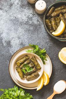 Dolma - foglie di vino greco ripiene (dolmades) su sfondo grigio cemento