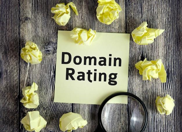 Concetto seo di valutazione del dominio - testo su fogli di nota gialli su una superficie di legno scuro con fogli accartocciati e una lente d'ingrandimento
