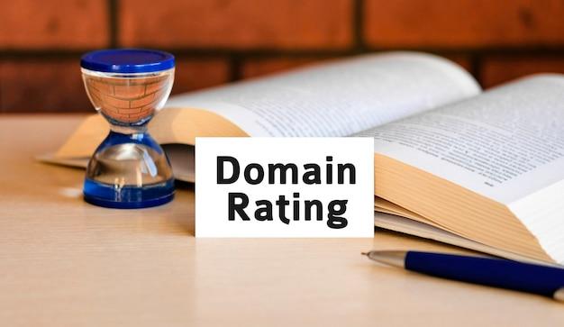 Testo di valutazione del dominio su una superficie bianca con una clessidra e un libro aperto