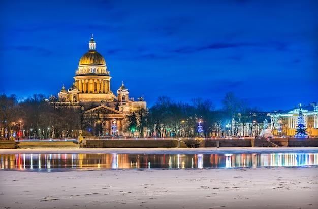 La cupola della cattedrale di sant'isacco e il fiume neva in ghiaccio a san pietroburgo in una notte blu invernale
