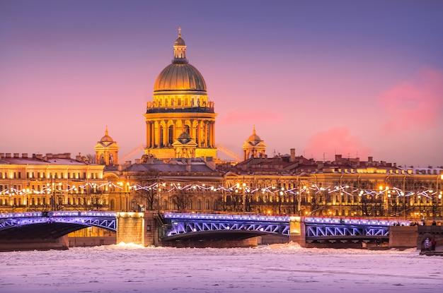 La cupola della cattedrale di sant'isacco, il ponte del palazzo e il fiume neva in ghiaccio a san pietroburgo in una notte lilla invernale