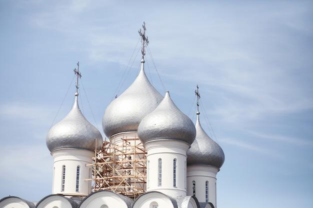Cupole di un edificio religioso. croci sulle cupole della chiesa. cattedrale con cupole d'argento contro il cielo