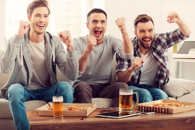 Tifosi domestici. tre giovani uomini felici che guardano la partita di calcio e tengono le braccia alzate mentre sono seduti sul divano