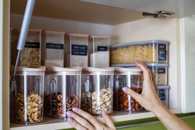 Organizzazione domestica di conservazione degli alimenti secchi vegetariani sani sullo scaffale dell'armadio della cucina