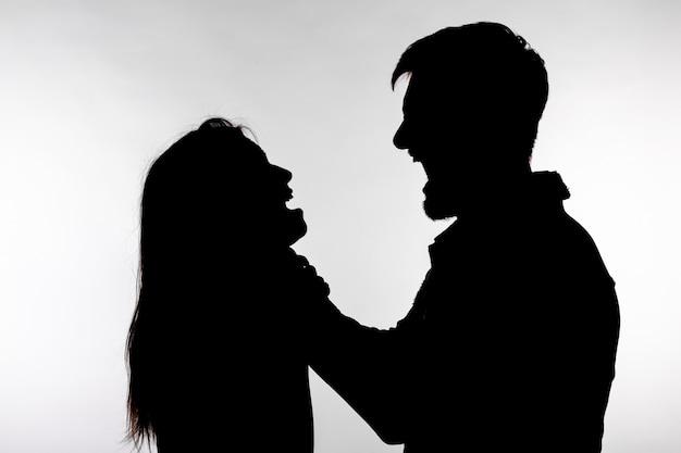 La violenza domestica e il concetto di abuso. sagoma di un uomo che asfissia una donna