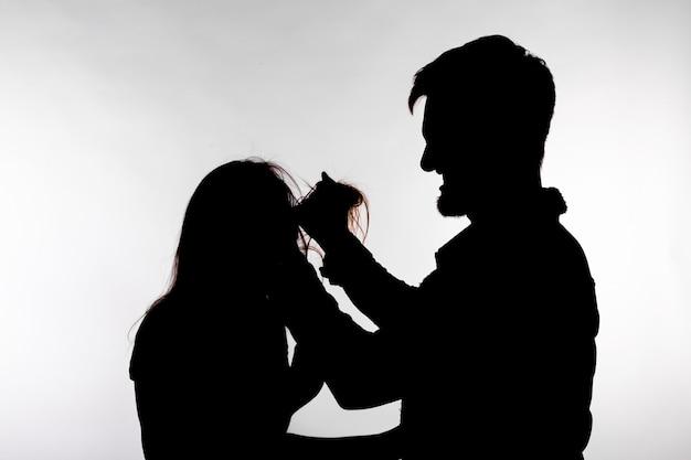 Violenza domestica e concetto di abuso - silhouette di un uomo che picchia una donna indifesa.