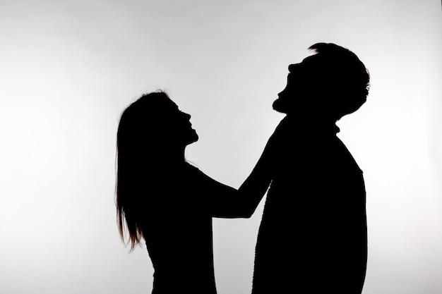 Violenza domestica e concetto di abuso - silhouette di una donna che asfissia un uomo.