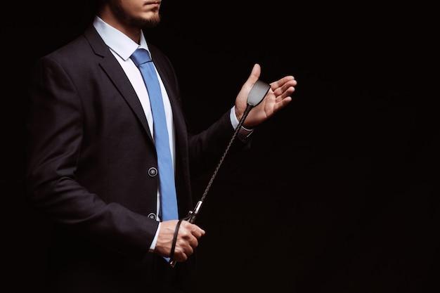 Uomo d'affari dominante in un vestito che tiene una frusta di cuoio