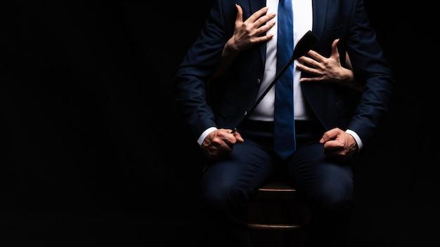 Uomo dominante con una frusta flogger e le mani della sua schiava sottomessa