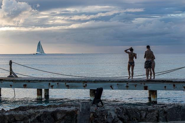Tramonto dominicano sul molo con gente che guarda il mare