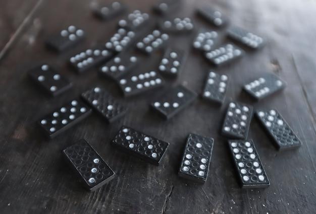 Pezzi del gioco del domino sparsi su una vecchia scrivania di legno
