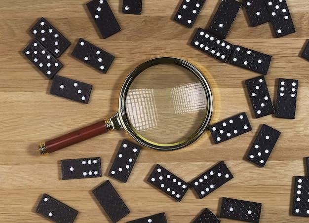 Pezzi del gioco domino sparsi sulla scrivania di legno con vista dall'alto della lente d'ingrandimento dorata