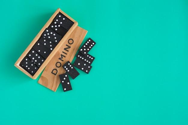 Gioco di domino in scatola di legno su sfondo verde vista dall'alto gioco da tavolo per famiglie