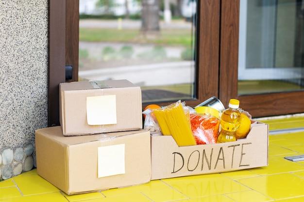 Dona una scatola con il cibo sulla porta di casa vicino alla porta di casa e alle cassette della posta