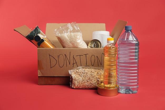 Scatola per donazioni. scatola di cartone aperta con vestiti e cibo su uno sfondo rosso