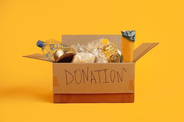 Scatola per donazioni. scatola di cartone aperta con vestiti e cibo su uno sfondo giallo.