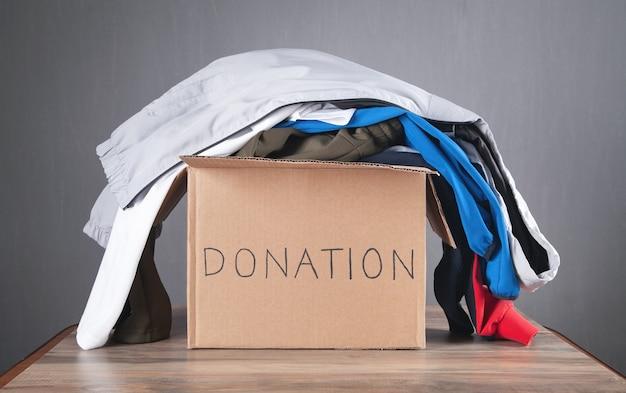 Scatola per donazioni con vestiti sul tavolo di legno.