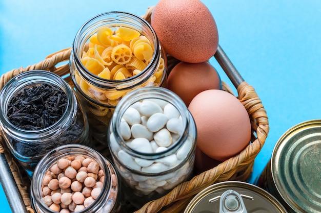 Scatola di donazione con uova, pasta, fagioli, ceci e tè in barattolo di vetro