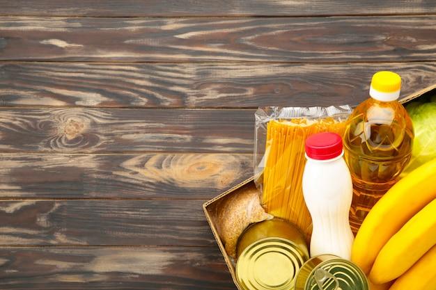 Scatola di donazione con cibo sullo sfondo marrone