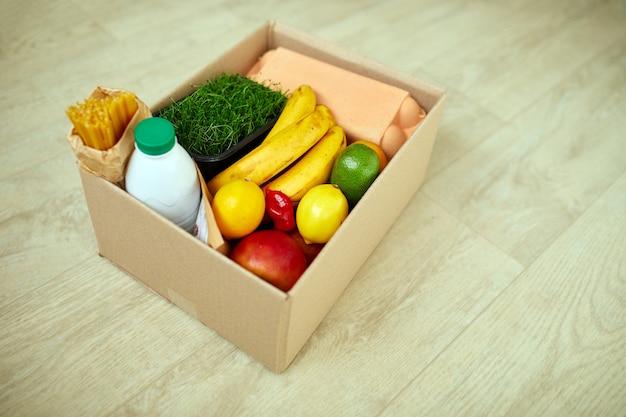 Scatola di donazione con cibo sul pavimento a casa, focolaio di coronavirus, autoisolamento, consegna, concetto di volontariato, consegna senza contatto.