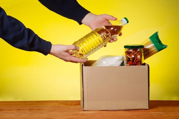 Scatola di donazione con cibo e mani di un volontario. spaghetti, grano saraceno, cibo in scatola, olio in una scatola. assistenza volontaria ai senzatetto e ai bisognosi. supporto sociale per le persone.