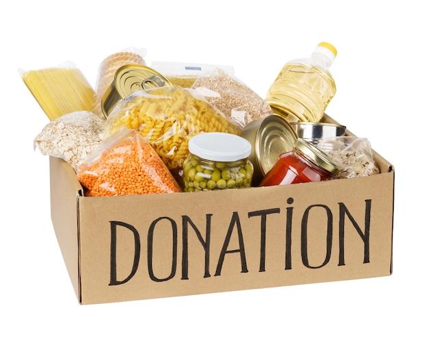 Scatola per donazioni con vari alimenti. scatola di cartone aperta con olio, cibo in scatola, cereali e pasta. isolato.