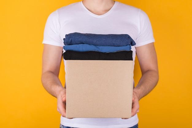 Concetto di donazione. foto vista frontale ritagliata dell'uomo che tiene una scatola di cartone piena di vestiti isolati su sfondo giallo