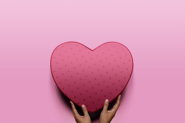 Concetto di donazione. mani del donatore che dà una scatola rossa del cuore a un destinatario