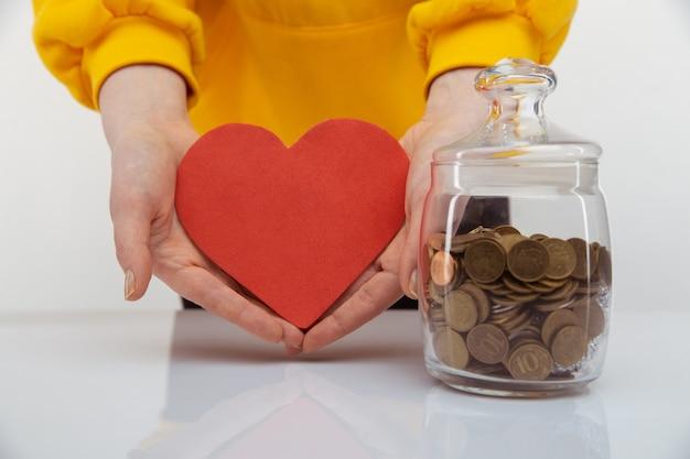 Concetto di donazione. donna che tiene cuore rosso nelle mani vicino al salvadanaio.