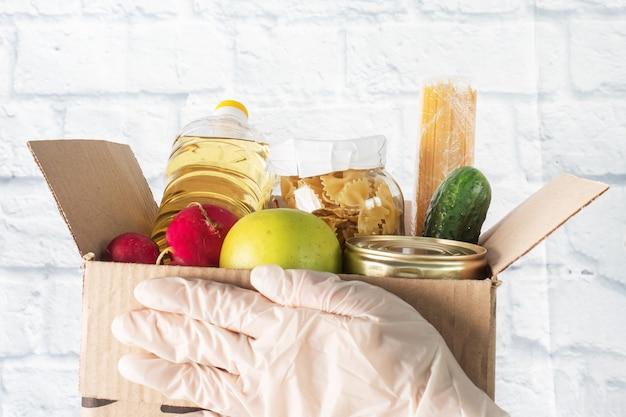 Donazione di cibo raccolto in una scatola. copia spazio.