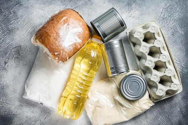Donazione di beni alimentari, concetto di aiuto in quarantena. olio, conserve, pasta, pane, zucchero, uova. sfondo bianco. vista dall'alto.