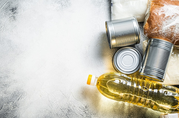 Donazione di beni alimentari, concetto di aiuto in quarantena. olio, conserve, pasta, pane, zucchero, uova. tavolo bianco. vista dall'alto. copia spazio.
