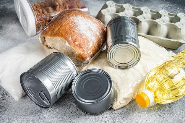 Donazione di beni alimentari, concetto di aiuto in quarantena. olio, conserve, pasta, pane, zucchero, uova. tavolo bianco. vista dall'alto.