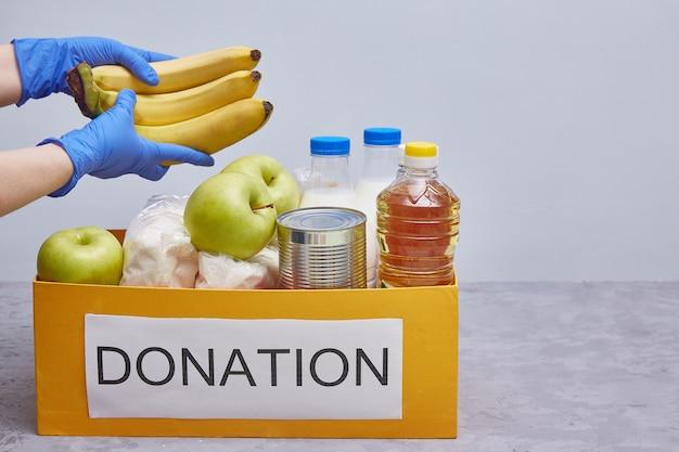 Donazione e materiale di aiuto alimentare durante la pandemia di coronavirus. le mani in guanti protettivi blu prendono o posano il cibo.