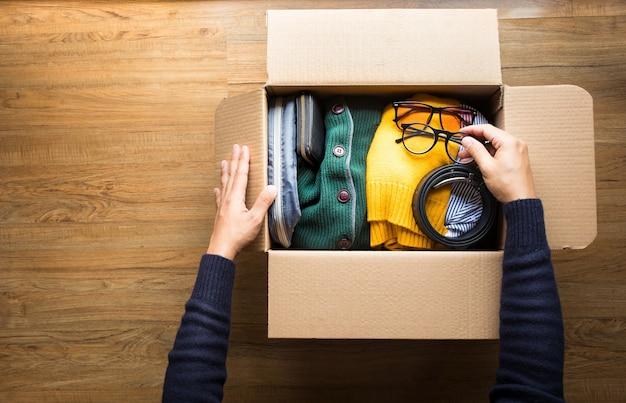 Donazione con il giovane che mette l'abbigliamento degli accessori nella scatola marrone