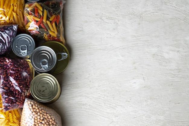 Donazioni di cibo con conserve in scatola sullo sfondo del tavolo. dona il concetto.